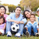 Multigenerational family on the lawn with a soccer ball.